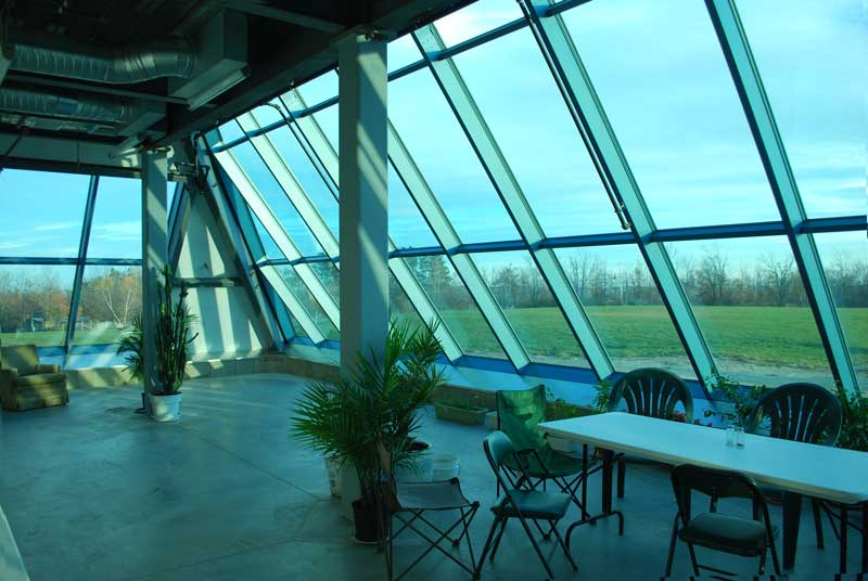 A shot from within the first floor of our glass-fronted pyramid. Though there are only a few plants right now, our greenhouse space will soon be filled to the brim with a wide variety of plants and flowers.